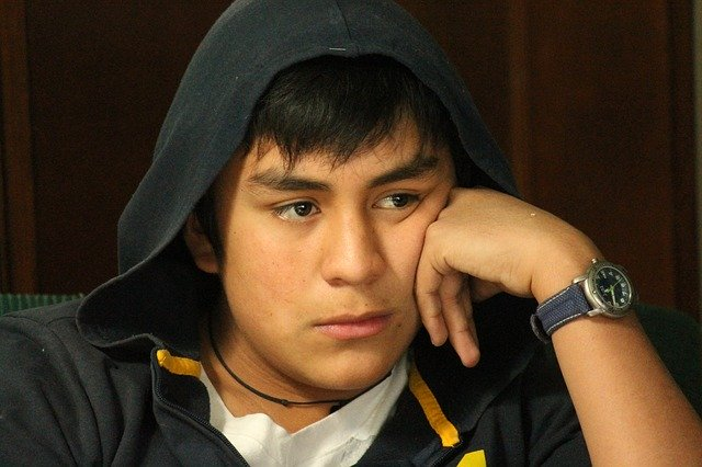 Zamyšlený mladík s kapucí přes hlavu